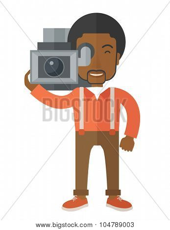 An african-american cameraman with video camera taking a video vector flat design illustration isolated on white background. Vertical layout.