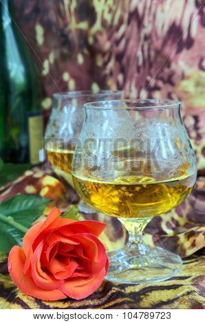 Two Glasses Of Cognac With Red Roses And A Bottle On A Colored Background