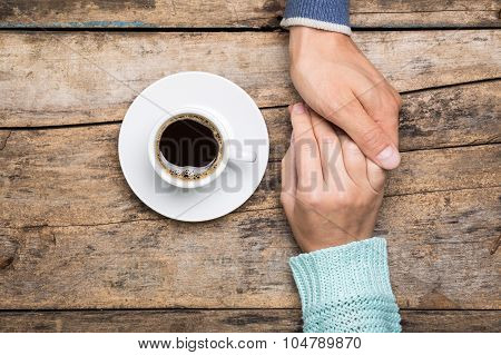 Man Holds Woman's Hand With Cup Of Coffee