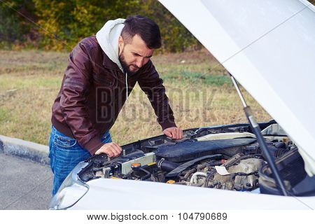worried man looking under the hood of breakdown car at outdoor