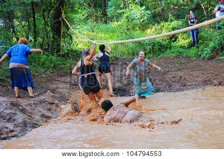 MUSKOGEE, OK - Sept. 12: Athletes try to go through muddy obstacle to avoid bloody zombies during the Castle Zombie Run at the Castle of Muskogee in Muskogee, OK on September 12, 2015.