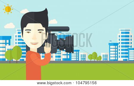 An Asian cameraman with video camera taking a video with buildings around vector flat design illustration. Horizontal layout with a text space.