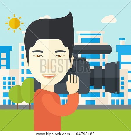 An Asian cameraman with video camera taking a video with buildings around vector flat design illustration. Square layout.