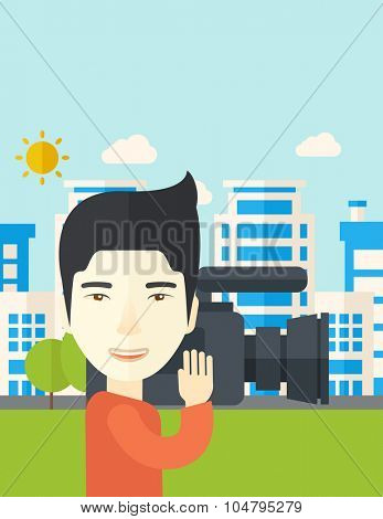 An Asian cameraman with video camera taking a video with buildings around vector flat design illustration. Vertical layout with a text space.