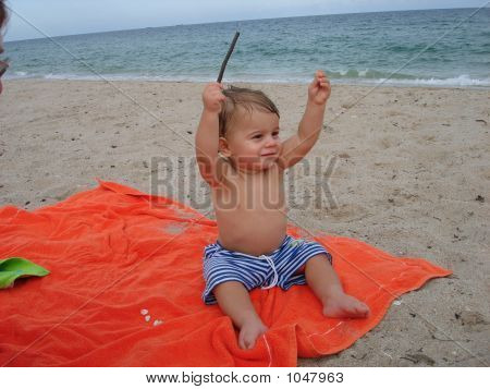 Baby With Arms Raised At The Beach