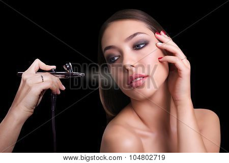 close portrait of a beautiful girl with make-up . Make up with airbrush. Isolated on black backgroun