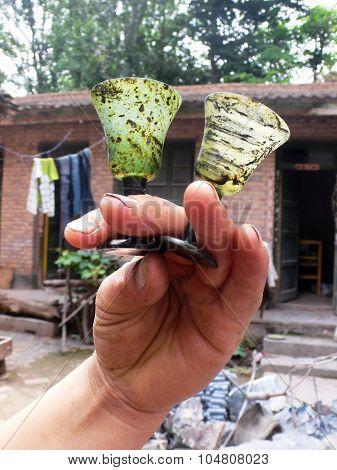 Hand holding tiny jade goblets