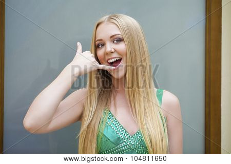 Call Me. Beautiful happy woman in green dress making a call me gesture, indoor