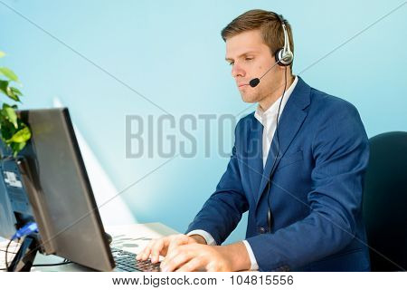 Young Customer Support Phone Operator with Headset Working on Computer in the Office.