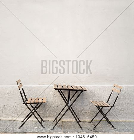 table and two chairs near the wall