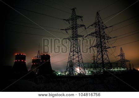 High-voltage power transmission towers in sunset sky