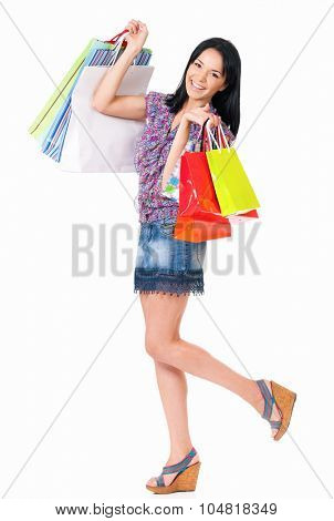 Young happy smiling woman with shopping bags, isolated over white background