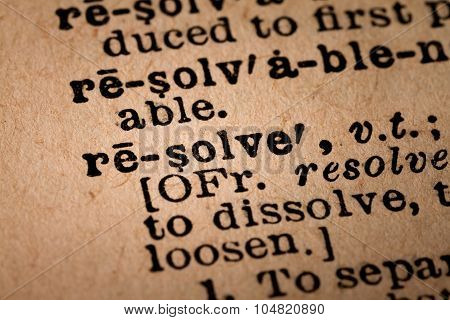 Close-up Of An Opened Dictionary Showing The Word Resolve