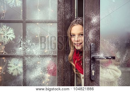 Child girl opens door and welcome guests, snow weather, house is decorated for Christmas