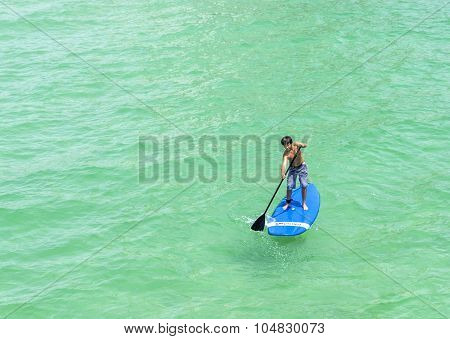 Boy Enjoys Stand Up Paddle Surfing  In The Ocean