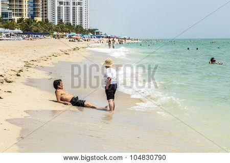 People Enjoy To Relax Near The Pier In Sunny Isles Beach