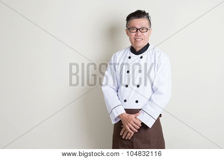 Portrait of 50s mature Asian male chef in uniform smiling, standing on plain background with shadow, copy space.