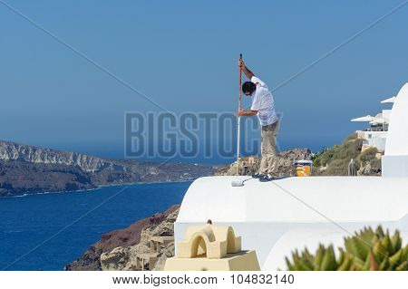 Man paints the roof of hotel on Santorini island