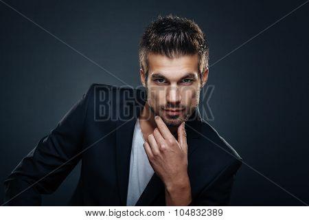 Portrait Of Handsome Man In A Studio On A Dark Background