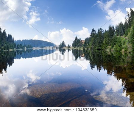 Blue expanse of clear forest lake with huge stones on the bottom pine forest and cloudy sky and their reflection in the water early in the morning in the Rhodope Mountains (Rhodopes Bulgaria)