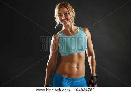 Athletic woman with dumbbell on dark background