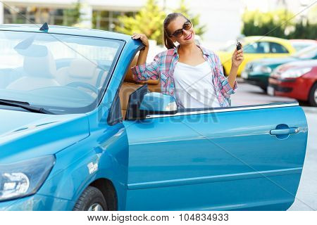 Woman In Sunglasses Standing Near Convertible With Keys In Hand - Concept Of Buying A Used Car Or A