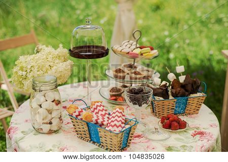 Dessert table for a party. Chocolate cake, cupcakes, sweetness, macaroons, marshmallows, zephyr and