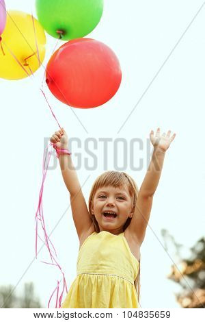 Little girl with balloons outside