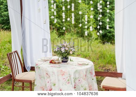 Outdoor gazebo with white curtains. Wedding decorations.