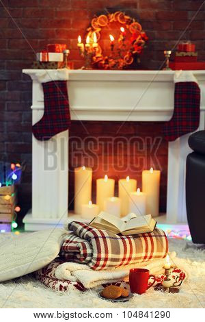 Composition with warm plaid, book, cup of hot drink on colorful lights background