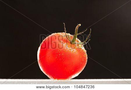 fresh washed tomato isolated on black background