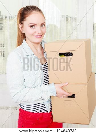 Woman Moving Into Apartment House Carrying Boxes.