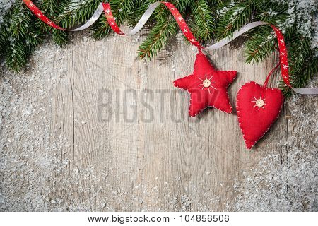Christmas Border. Tree branches with stars, heart and snow on wooden board