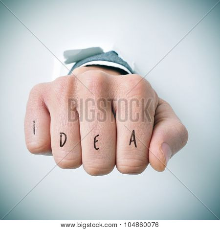 a young businessman breaks through a wall with his fist, and the word idea written in his knuckles