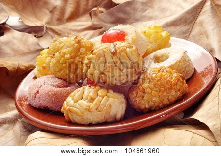 an earthenware plate with some different panellets, typical pastries of Catalonia, Spain, eaten in All Saints Day, on a surface full of dry leaves
