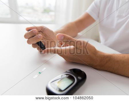 medicine, diabetes, glycemia, health care and people concept - close up of man checking blood sugar level by glucometer at home