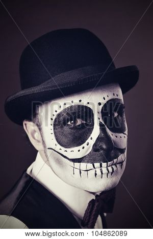 portrait of a man with calaveras makeup, wearing bow tie and bowler hat, with a vintage effect