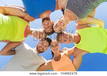 fitness, sport, friendship and healthy lifestyle concept - group of happy teenage friends or sportsmen in circle outdoors