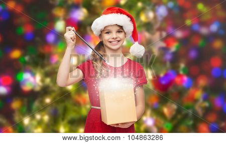 christmas, winter, holidays and childhood concept - smiling girl in santa helper hat with gift box and magic wand over glitter or lights background