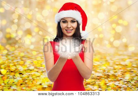 people, holidays, christmas and magic concept - beautiful sexy woman in santa hat and red dress with fairy dust on her palms over yellow lights or golden confetti background