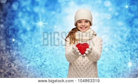 christmas, winter, holidays and childhood concept - smiling teenage girl in winter clothes with small red heart over blue glitter or lights background