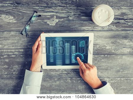 business, people, finances and technology concept - close up of hands pointing finger to tablet pc computer screen with bitcoin, coffee cup and eyeglasses on table