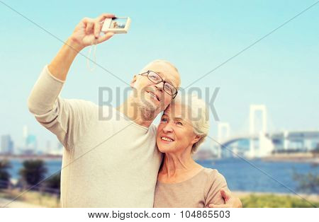age, tourism, travel, technology and people concept - senior couple with camera taking selfie on city street over rainbow bridge in tokyo and river background