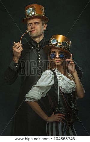 The Couple Steampunk. A Man With A Pipe And A Girl With Glasses And Hat