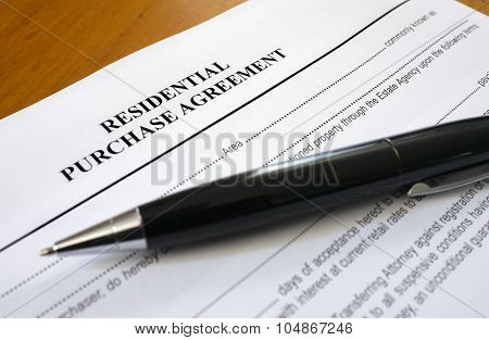 pen lying across a residential purchase agreement