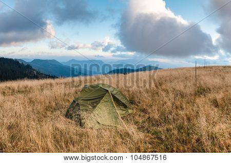 Tent On Mountain Meadow Under Morning Cloudy Sky