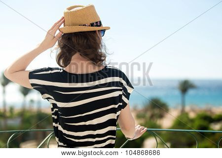 Young Woman Looking At Sea From Balcony
