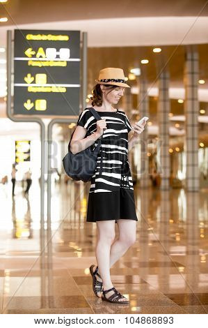 Woman Using Smartphone App In Airport