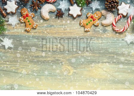 Christmas decoration with gingerbread cookies,fir branches and spices on the old wooden board