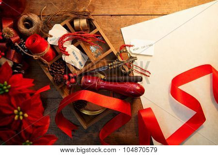 Christmas preparation. Tray with ribbons and christmas tags, on an old wooden table with blank white paper copyspace. Vintage feel. Warm incandescent lighting.